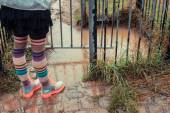 Young woman in boots standing by puddle — Stock Photo