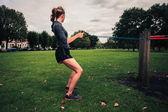 带阻力时在公园里锻炼的女人 — 图库照片