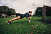 Woman working out with resistance band in the park — Stock Photo