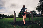 Young woman stretching her legs in the park — Stock Photo