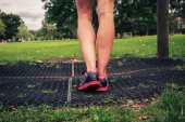The legs of a young woman by fitness equipment — Stock Photo