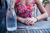Woman sitting at table with jug of water — Stock Photo