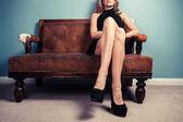 Sexy woman in heels on sofa — Stock Photo