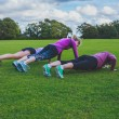 Three women doing push ups in park — Stock Photo #57066593