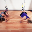 Two women working out with straps in gym — Stock Photo #57068349