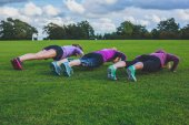 Three women doing push ups in park — Stock Photo