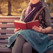 Young woman sitting on park bench with book — Stock Photo #57097383