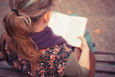 Young woman sitting on park bench with book — Stock Photo
