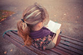 Young woman sitting on park bench with book — Foto Stock