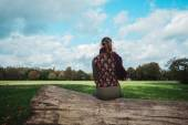 Woman sitting on a fallen tree in the park — Stock Photo
