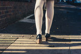 The legs of a woman walking in the street — Stock Photo