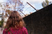 Woman by wall with barb wire — Stock Photo