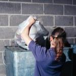 Woman putting rubbish in bin — Stock Photo #57136587