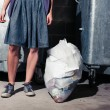 Woman standing next to bins with a bag of rubbish — Stock Photo #57137281