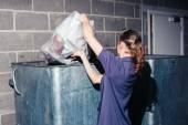 Woman putting rubbish in bin — Stock Photo