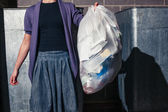 Woman standing next to bins with a bag of rubbish — Stock Photo