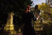 Redhead woman performing ritual at grave — Stock Photo