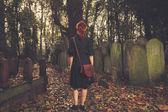 Woman walking amongst tombstones — Stock Photo