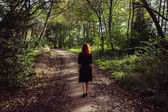 Young woman walking in forest — Stock Photo