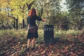 Woman disposing litter in the forest — Stock Photo