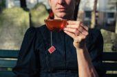 Woman drinking tea on cemetery — Stock Photo