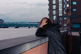 Sad woman by river in city — Stock Photo