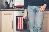 Man with bottle of wine in kitchen — Stockfoto