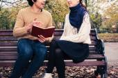 Man reading for woman on park bench — Stock Photo