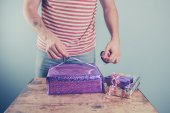 Man at table wrapping presents — Stock Photo