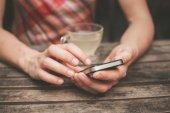 Jonge vrouw drinken thee en het gebruik van haar telefoon — Stockfoto