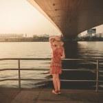 Young woman under bridge at sunset — Stock Photo #64284229