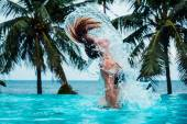 Sexy woman doing hairflip in swimming pool — Stock Photo