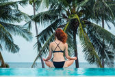Young woman meditating by swimming pool — Stock Photo
