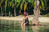 Woman sitting up against tree on tropical beach — Stock Photo