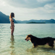 Woman with dog on tropical beach — Stock Photo #64691971
