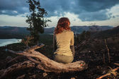Woman sitting on a burned hill — Stock Photo