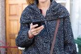 Woman outside house using phone — Zdjęcie stockowe