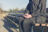 Woman using her phone by water in park — Stock Photo