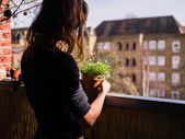 Woman attending to her plants on balcony — Stock Photo