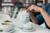 Young woman pouring a cup of tea — Stock Photo
