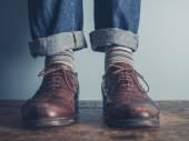Feet of a man on wooden floor — Stock Photo