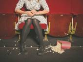 Woman in theater with popcorn on the floor — Stock Photo