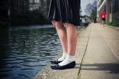 Young woman standing by a canal — Stockfoto