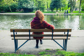 Woman sittng on bench by a pond in the park — Stock Photo