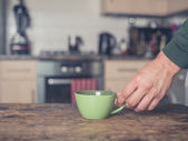 Hand placing cup on table — Stock Photo