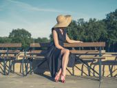 Elegant young woman sitting on park bench — Stock Photo