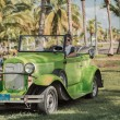 Green vintage classic car with a young taxi driver at Cuban tropical garden — Stock Photo #52926585