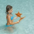 Joyful little girl sitting in azure crystal clear ocean and looking at starfish — Stock Photo #52926715