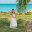Smiling joyful little girl standing in gorgeous tropical garden against azure tranquil ocean and blue sky background — Stock Photo #52926735