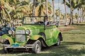 Green vintage  classic car with a young taxi driver at Cuban tropical garden — Stock Photo
